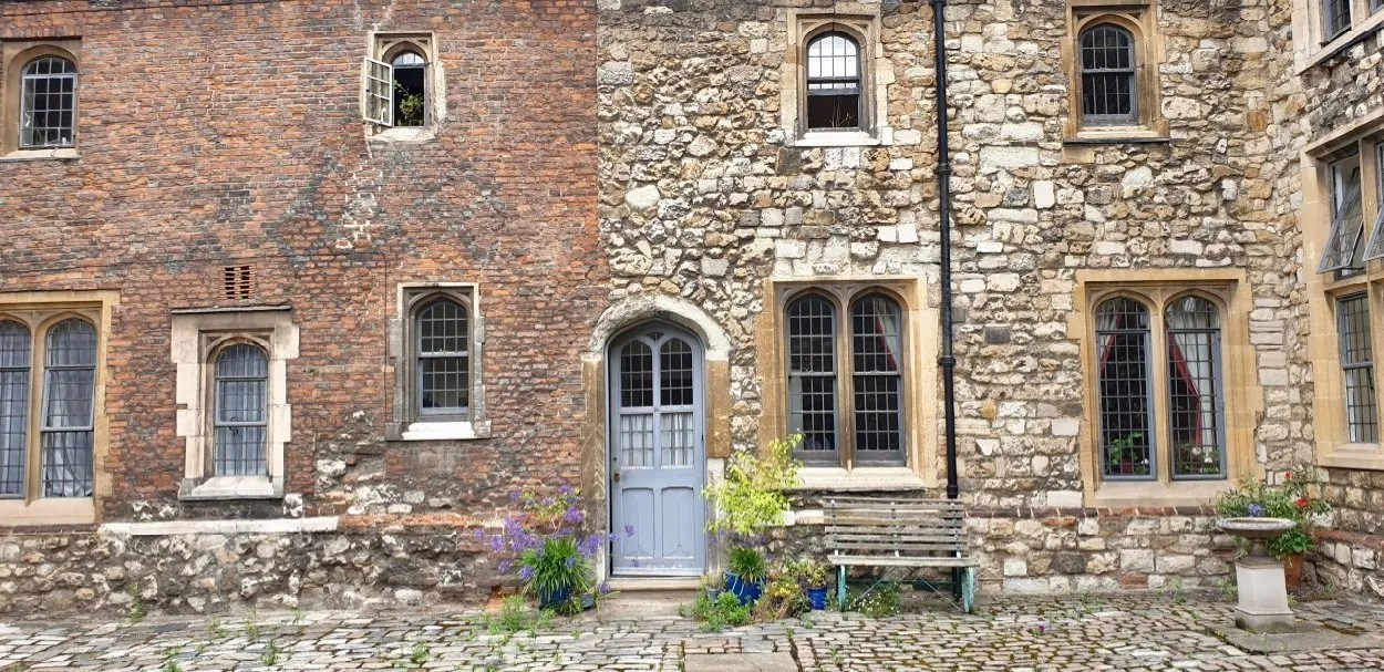 Tudor almshouses at Charterhouse London Blue door with flowers, mixed brick and stone wall
