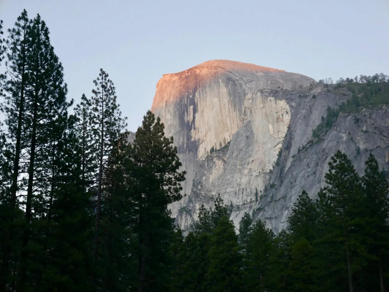 Tip of Yosemite half dome glowing red at sunset