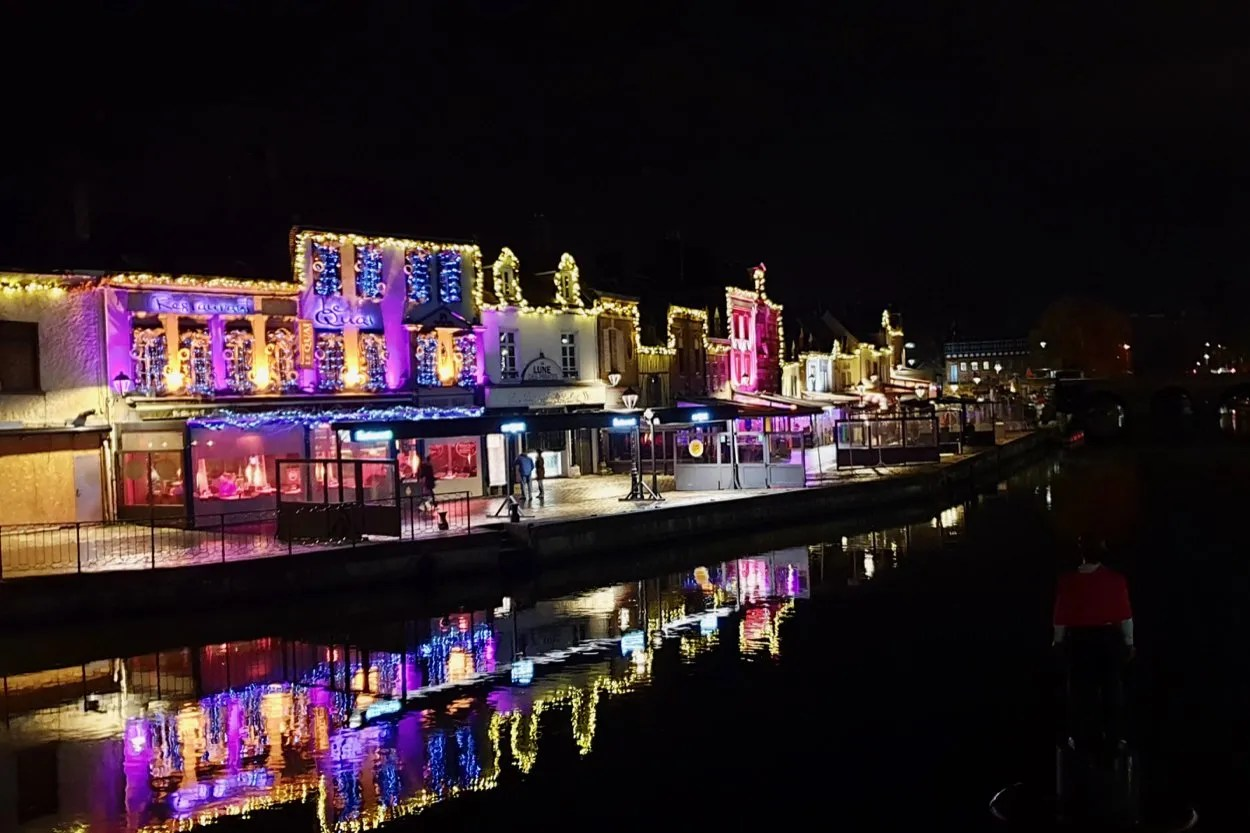 buildings lit with fairy lights reflected in the river Somme Amiens