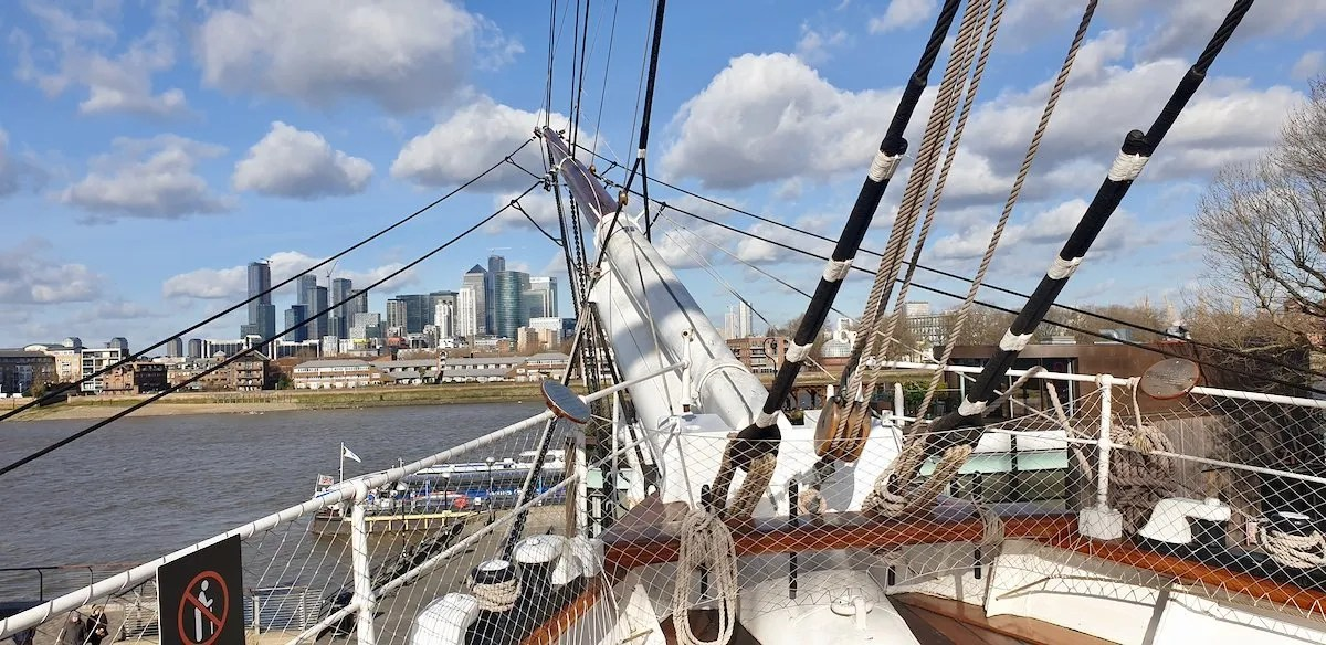 View from prow of Cutty Sark with rigging in foreground and Canary Wharf in the distance