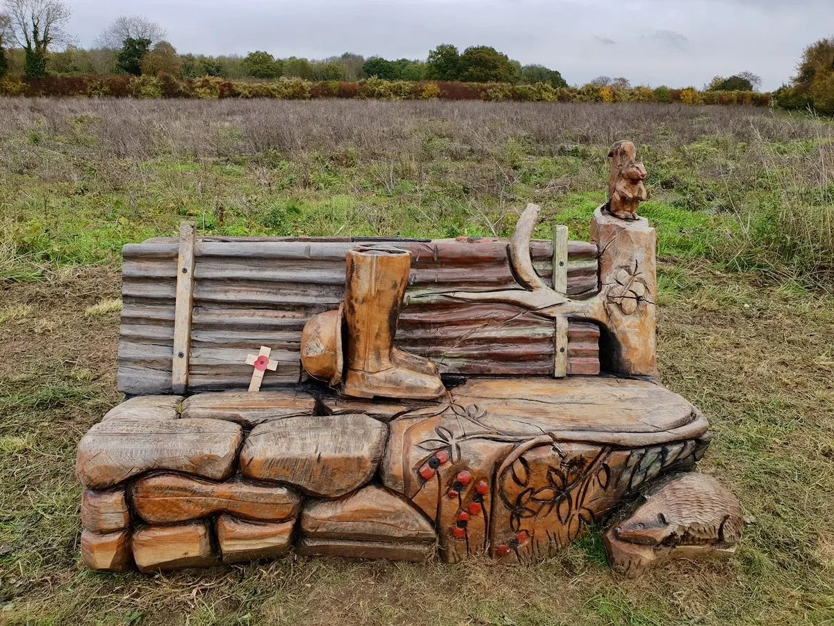 Carved bench with poppies, squirrel and soldiers boot in Langley Vale Wood