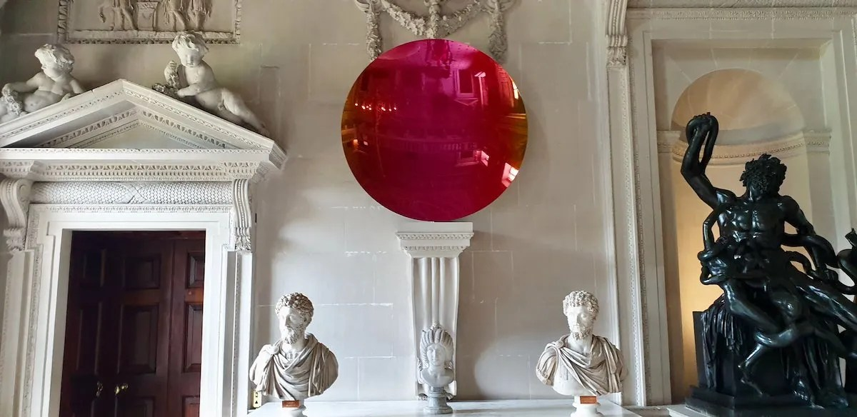 Stone Hall at Houghton Hall with red reflective mirror by Anish Kapoor