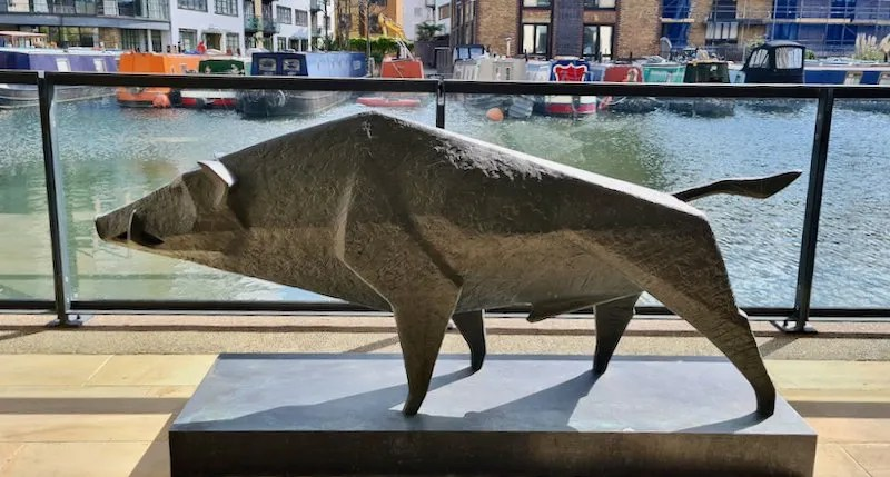 Bronze sculpture of a Boar with canal boats behind. Boar II by Terence Coventry