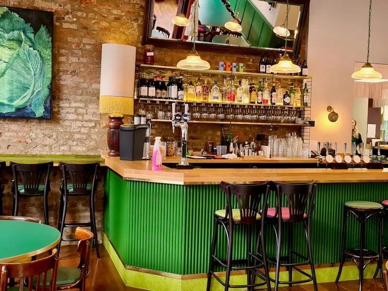 Green bar with bar stools and mirror