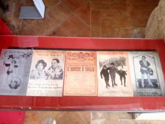 Inserti di giornali dell'epoca e una locandina del Barbiere di Siviglia messa in scena al Teatro La Scala di Milano.