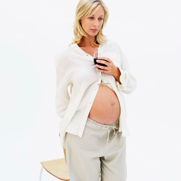 Pregnant woman holding a glass of red wine