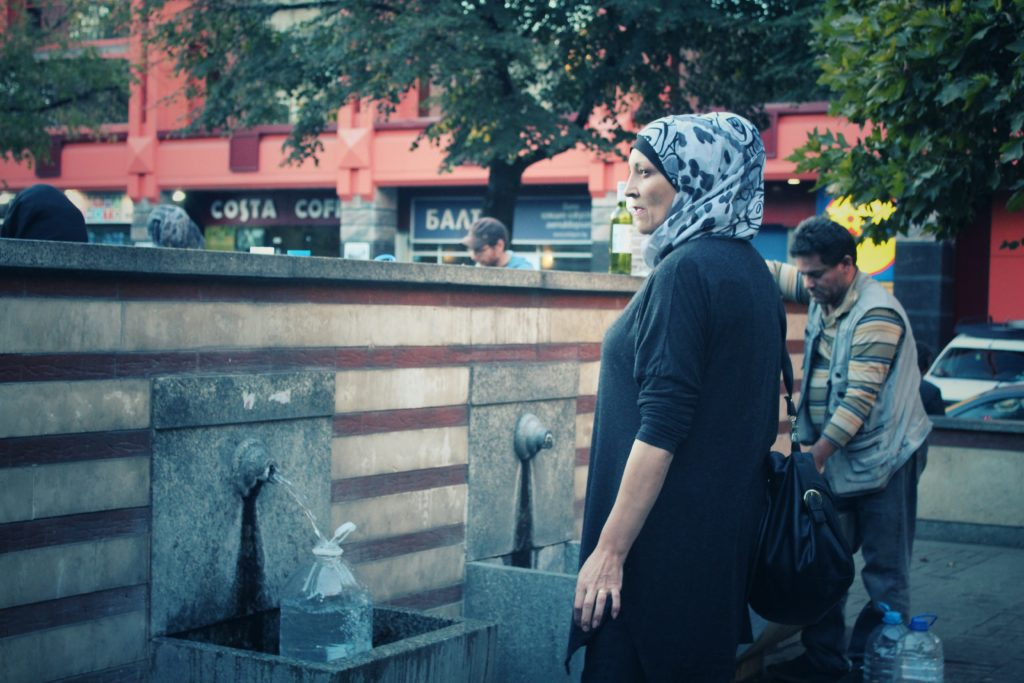 A woman fills a water jug at the natural springs in downtown Sofia, Bulgaria.
