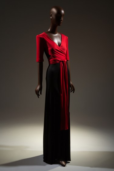 Two-tone evening dress in red and black rayon jersey; red top with deep V-neck, short sleeves padded at cap, attached vest panel with wrap and tie extensions; long flared black skirt.
