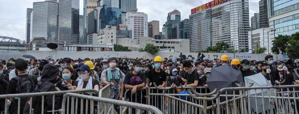 Hong Kong protestors stand at silver barricades protesting with city in the background