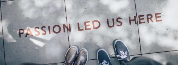 """red text on concrete sidewalk that says """"Passion led us here"""" two people's shoes can be seen in the shot"""