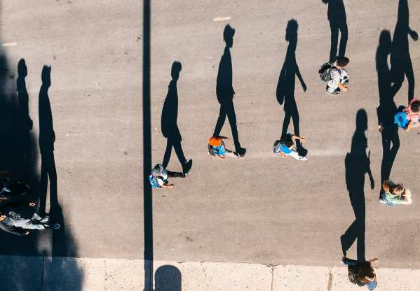 An overhead photo of people walking in the same direction on a street.