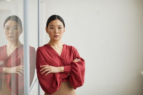 Serious Asian woman with hair pulled back and wide rim glasses in red top, arms crossed in front of chestl-leaning against a whiteboard