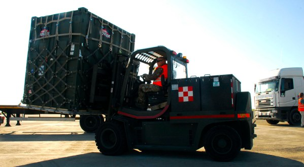 A black truck carrying medical supplies is driving. The road is mostly made of dirt and the weather is dry and sunny, there are two men in orange vests in the photo.