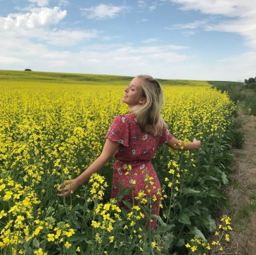 Image is of the subject, Kira Gregory in a flower field.