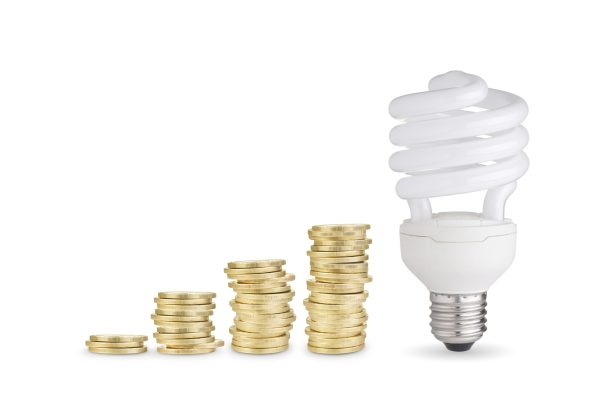 stacks of coins and energy saver bulb