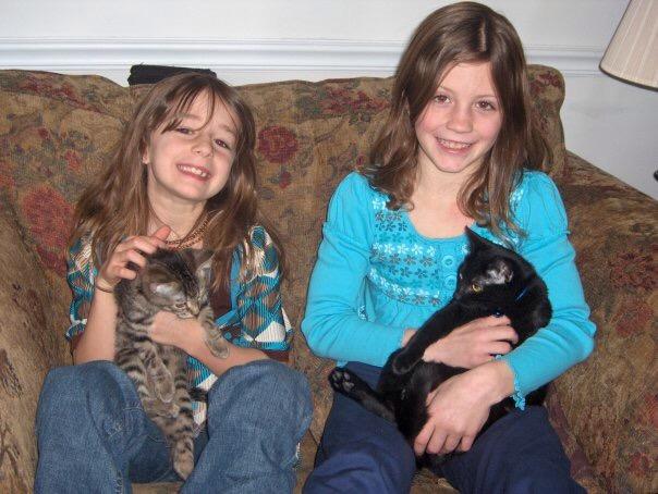 Adams and her sister sitting on a tan and red floral couch holding cats. Adams is wearing a turquoise and brown top with jeans. Her sister has a teal long sleeve with navy pants. This was early on after moving to Kansas