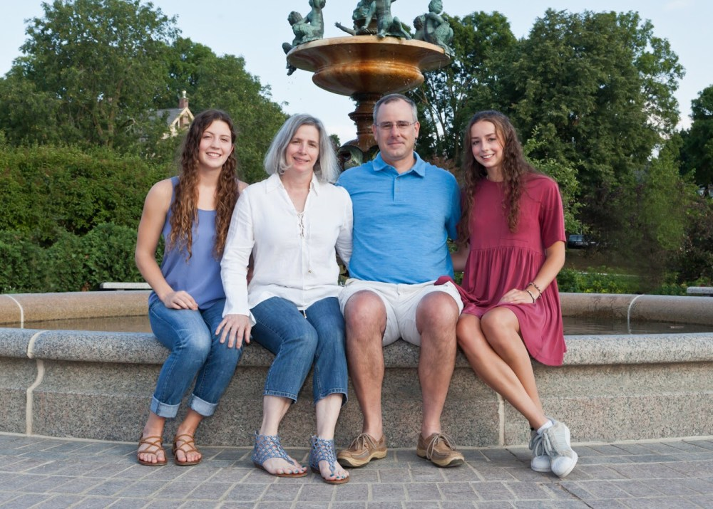 Adams and military family sitting on a fountain in the summer.