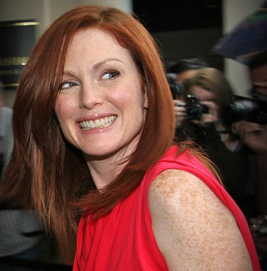 Actress Julianne Moore smiling in a red dress, People in the back take photos of her. Taken at the Toronto International Film Festival