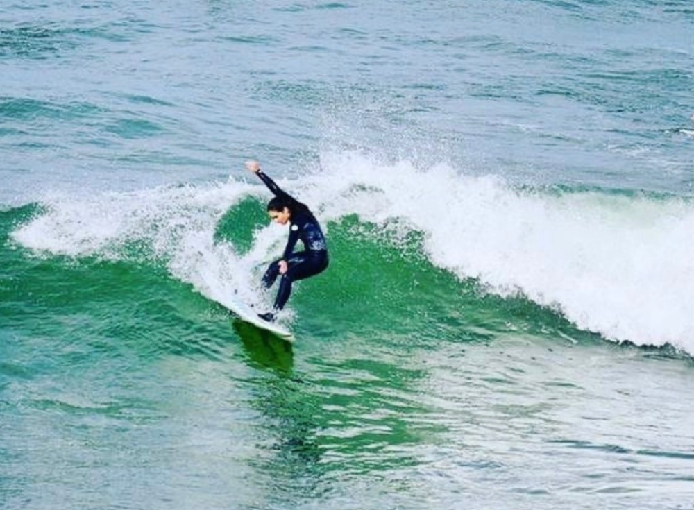 Kainoa Smith surfing on a wave in Tahiti.