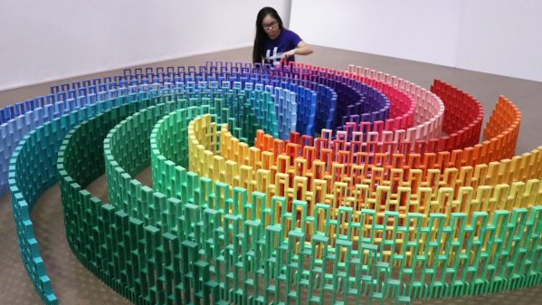 young woman starting a large rainbow domino