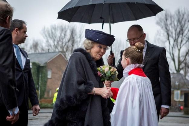 Een lid van de koorschool heet prinses Batrix van harte welkom in de basiliek Sint Bavo