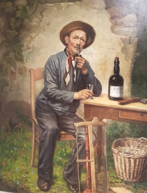 Wittenonnenstraat Hasselt, Nationaal Jenevermuseum, Hasselt, Emile Zickwolff (1860-1917), Man aan tafel met fles Hasselts vuur,. Olieverf op doek, Schrijnwerker geniet na het werk van een jenever.