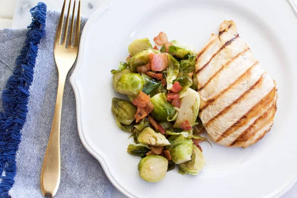 sauteed brussels sprouts with bacon on a plate with chicken
