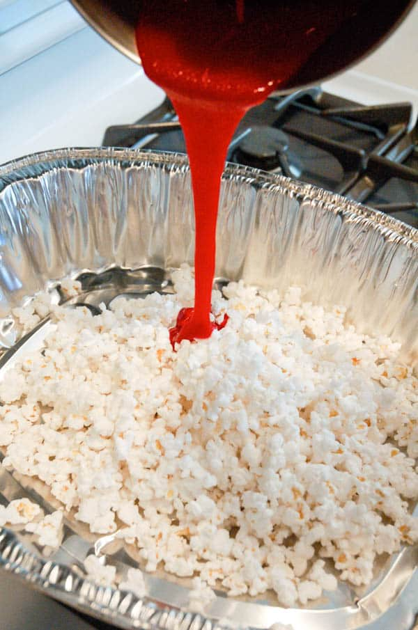candy coated popcorn recipe being made in a metal pan