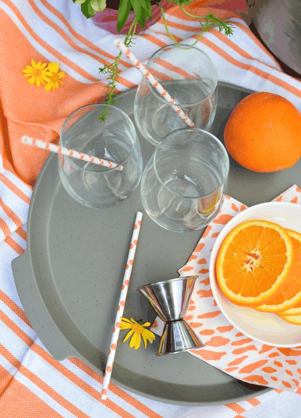 Polka dot paper straws and orange garnish for Aperol Spritzes.