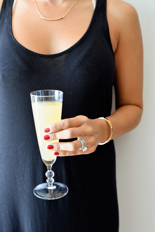 Girl holding a spiced pear bellini at a party.