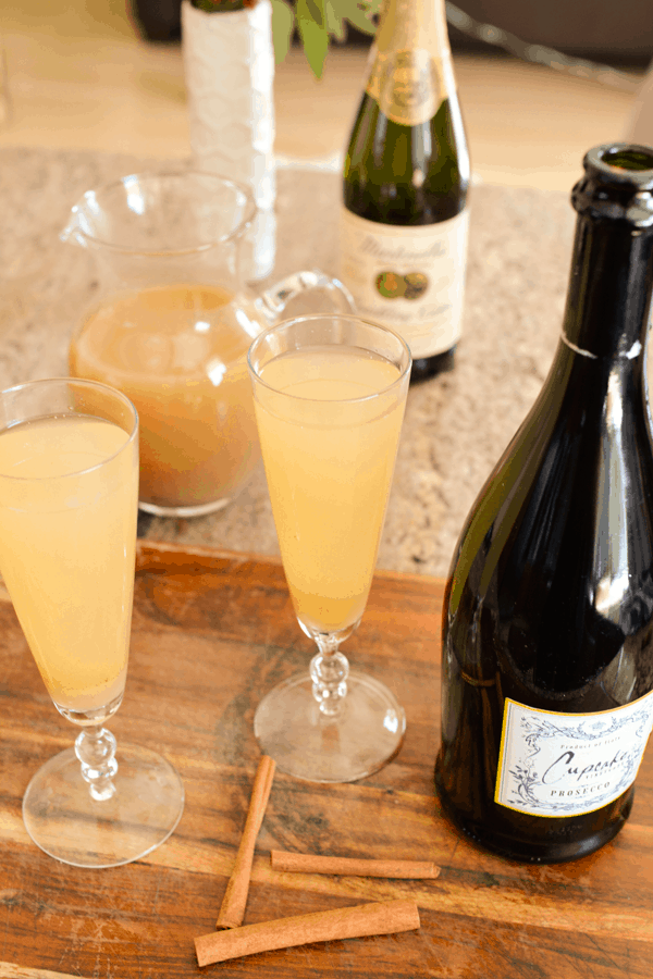 Two spiced pear bellinis in champagne flutes on a cutting board with other ingredients