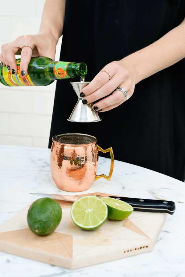 Pouring ginger beer for a absolut vodka mule recipe