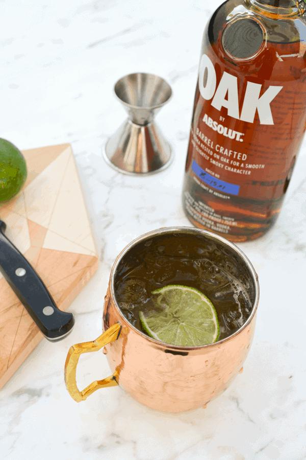 Oak by Absolut vodka mule in a copper mule mug on a table.