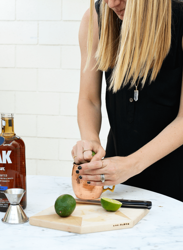 squeezing fresh lime juice for a oak by absolut cocktail