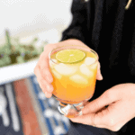 Peach paloma recipe in clear cocktail glass held by a woman in black shirt.