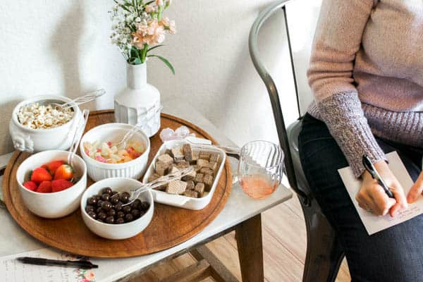 woman making notes about wine on a page next to bowls with candy.
