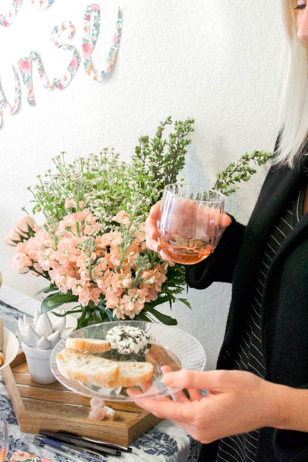Woman holding a glass of rose and a plate of food.