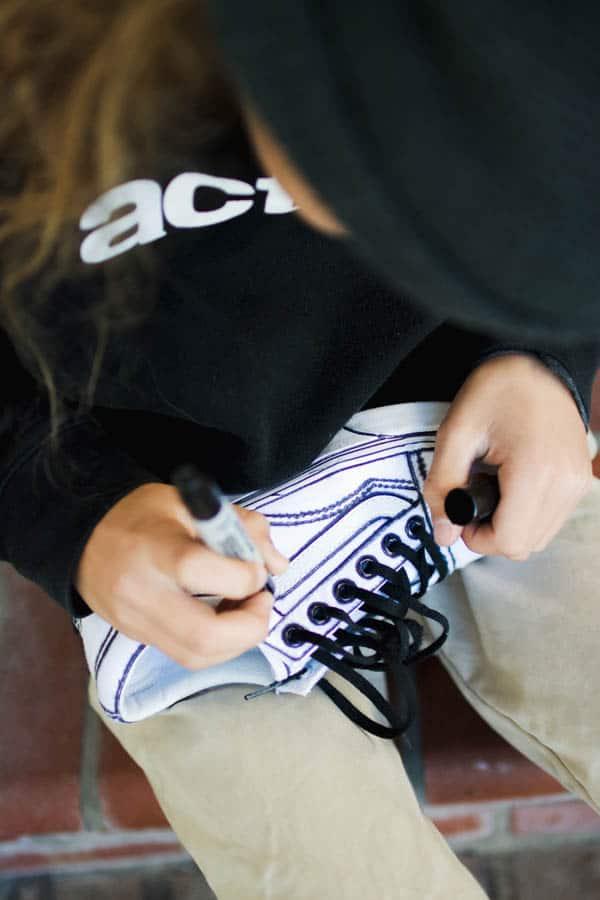 Boy using sharpie to make streetwear Vans sneakers.