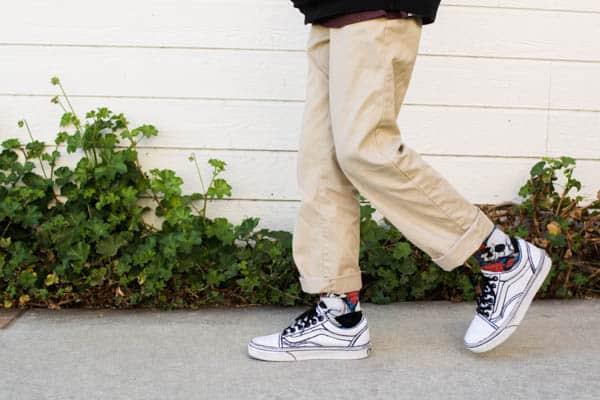 Boy in outlined Vans sneakers walking.