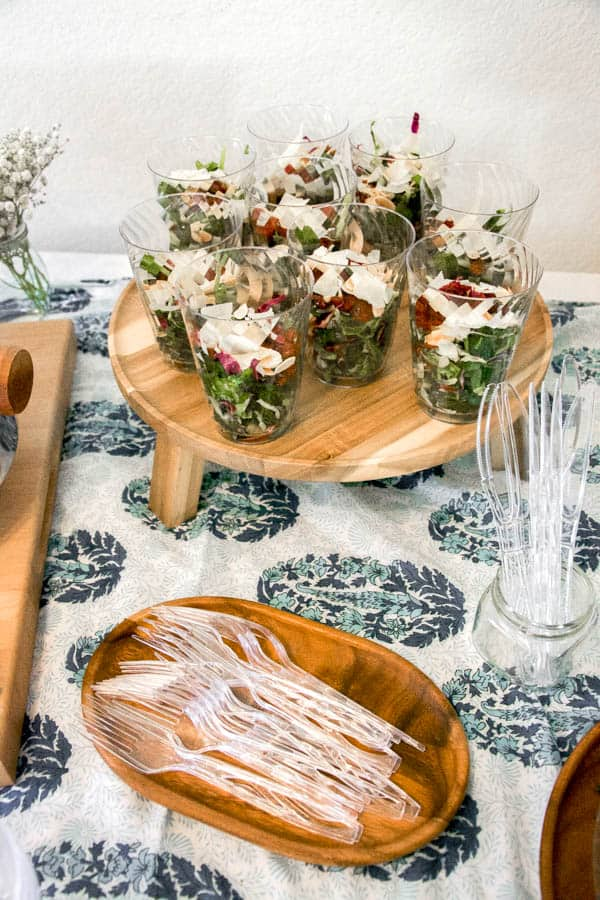 Salad in cups on a wood tray.