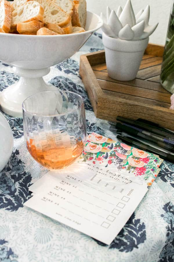 A wine tasting card for taking notes next to a glass of rose.