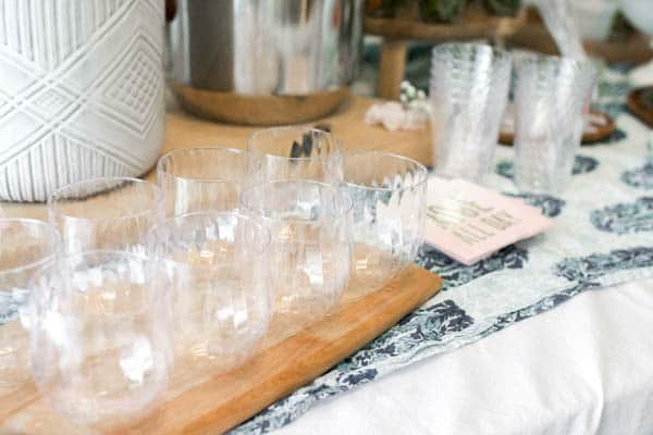 Plastic stemless wine glasses lined up on a table.