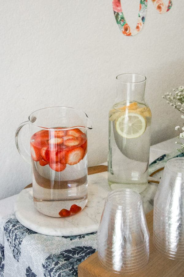 Pitchers of water on a table with sliced fruit in them.