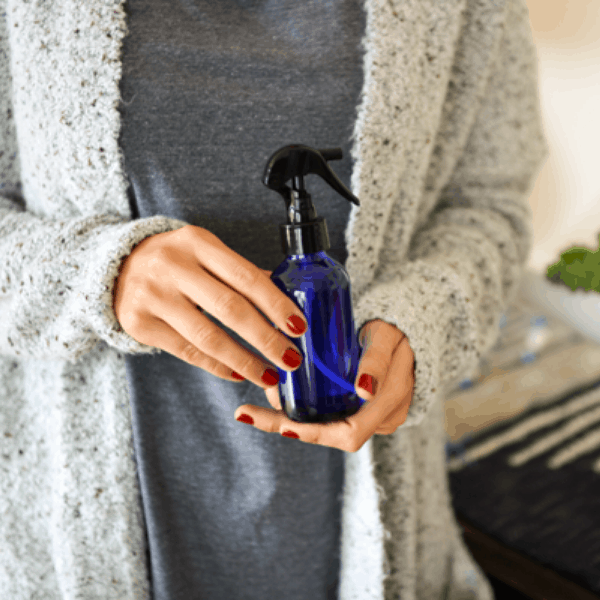woman holding essential oil room spry for good vibes to promote wellness and self care