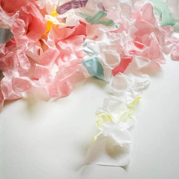 diy ruffled streamers from plastic tablecloths on a table for party decorations