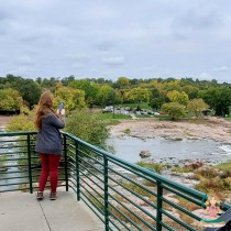 Angela taking photos of a scenic area by a river and trees