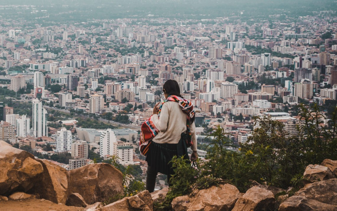 what to pack for travel photography cochabamba city cityscape bolivia development indigenous woman stands on cliff