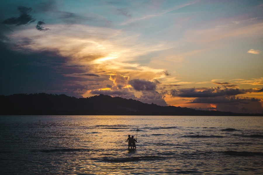 2 boys fishing at sunset in puerto viejo, costa rica