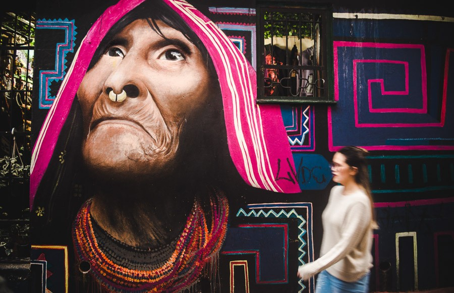girl in a sweater next to graffiti in candelaria: what to wear in bogota colombia