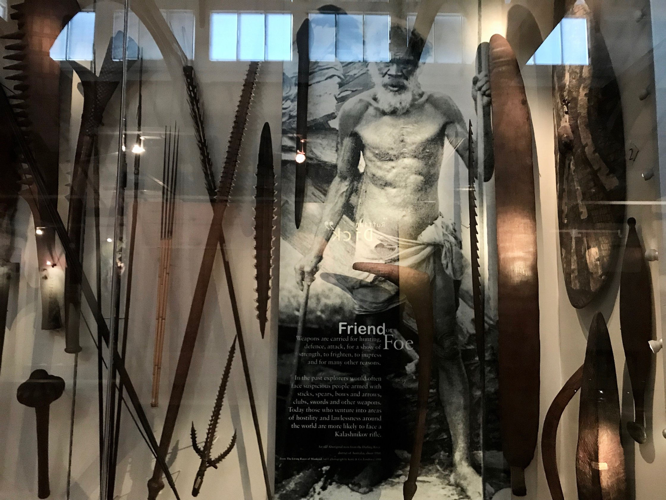 Museum vitrine showing a display of weapons from around the world with a photograph of a man entitled 'Friend or Foe'.